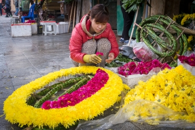 A young woman makes a floral funeral wreath.